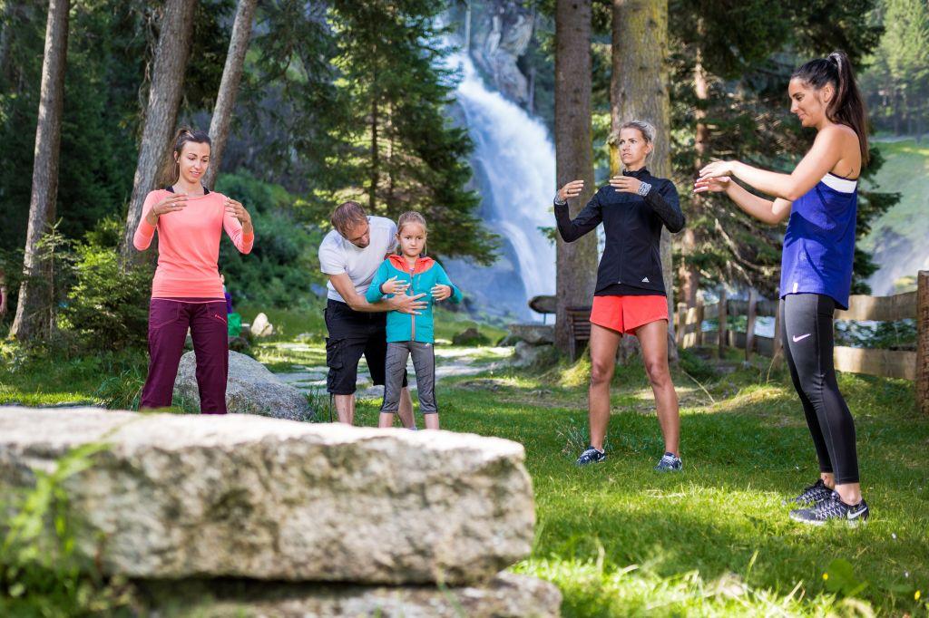Entspannungstechniken in der Gruppe vorm Wasserfall (Tourismusverband Krimml)