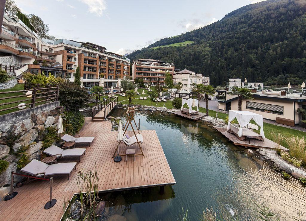Naturbadeteich mit Doppelliegen im Sommer (Sport & Wellness Resort Quellenhof)