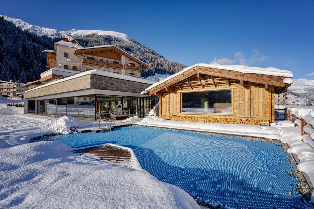 Naturschwimmteich mit Außensauna im Winter (Alpinhotel Berghaus)
