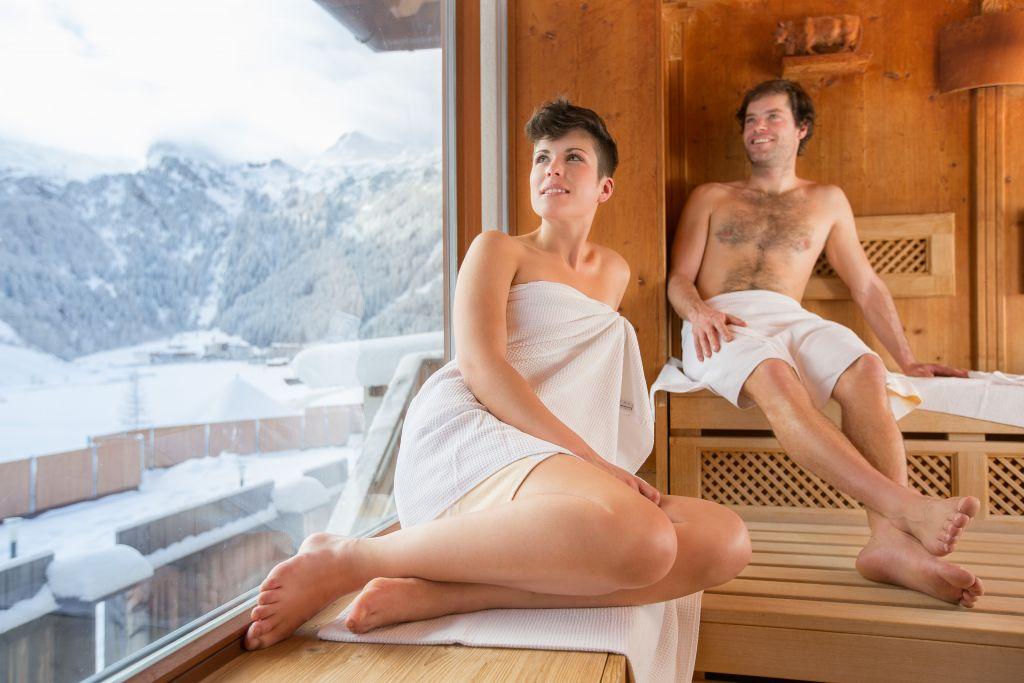 Paar in der Sauna mit Ausblick auf Winterlandschaft (Klausnerhof)