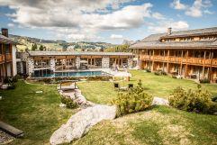 Außenanlage mit Outdoorpool im Sommer (Tirler-Dolomites Living Hotel)