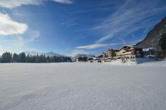Aussenansicht auf das winterlich eingeschneite Hotel (Alpina Kössen)
