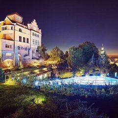 Aussenansicht mit beleuchtendem Outdoorpool bei Nacht (Schloss Mönchstein)