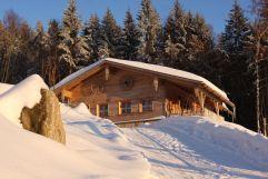 Außenaufnahme des Chaltes in verschneiter Winterlandschaft (Hüttenhof - Wellnesshotel und Luxus-Bergchalets)