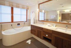 Badezimmer im modernen Design mit Badewanne und Waschtisch im Hotel Trofana Royal
