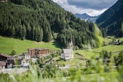 Blick auf das Naturhotel Rainer eingebettet in sommerliche Bergwiesen (Naturhotel Rainer)
