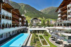 Blick in den Innenhof mit Bergpanorama und Pool im Sommer (Hotel Trofana Royal)