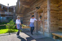 Die Gastgeberinnen überbringen den Frühstückskorb persönlich an die Gäste (Alpzitt Chalets)