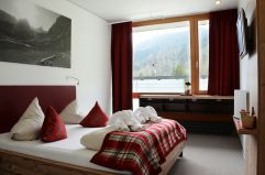 Doppelbettzimmer mit roten Interieur (MyTirol)