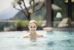 Frau beim Schwimmern im Pool (Sport & Wellness Resort Quellenhof)