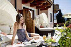 Frau entspannt im Außenbereich im Sommer (Biohotel Castello Königsleiten)