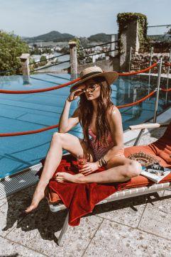 Frau genießt Sonne  auf der Liege am Outdoor Pool (Schloss Mönchstein)