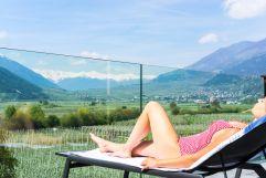 Frau genießt Sonnenbad auf der Panoramaterrasse im Sommer (Wanderhotel Vinschgerhof)
