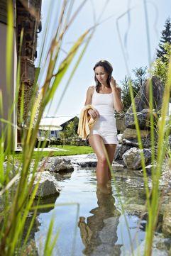 Frau im Naturbadeteich im Sommer (Biohotel Castello Königsleiten)