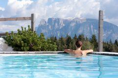 Frau im Pool genießt Bergblick (Hotel Tann)