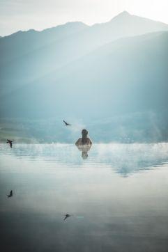 Frau im Sky Pool mit traumhaftem Ausblick (Alpin Panorama Hotel Hubertus)