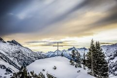 Gipfelkreuz bei Sonnenuntergang im Winter (c) ratko-photography (Benglerwald Berg Chaletdorf)