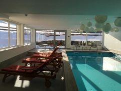 Hallenbad mit Blick auf die verschneite Winterlandschaft (Hotel Gemma - Kleinwalsertal Hotels)