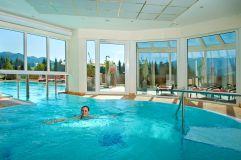 Indoorpool mit Aussicht im Hotel Alpina