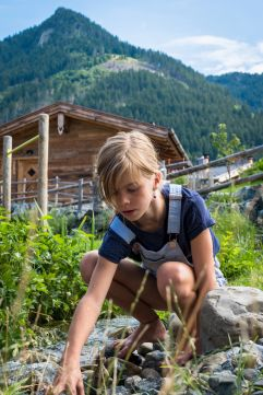 Kind entdeckt die alpine Natur am Bergbach (c) Fotostudio Wälder (Alpzitt Chalets)