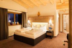 Komfortables Schlafzimmer der Deluxe Suite (Alpinhotel Berghaus)
