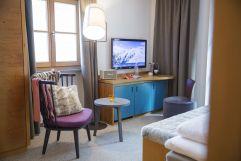 Lichtdurchfluteter Sitzbereich mit großem Fernseher (c) Johanna Gunnberg (VALLUGA Hotel)