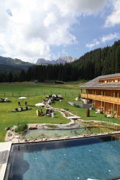Natur-Badeteich und Outdoorpool mit großer Liegewiese im Hotel Tirler (Tirler- Dolomites Living Hotel)