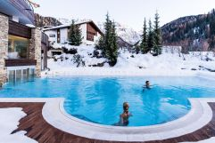 Outdoor-Pool in verschneiter Umgebung (Hotel Granbaita Dolomites)