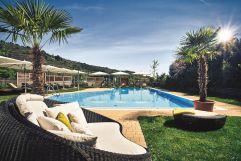 Outdoorpool mit Palmen und Strandliegen im Steigenberger (winzerhotels)