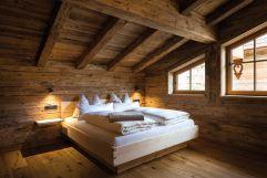 """Schlafzimmer mit Hüttenflair im Komfort-Chalet """"s´kommodè"""" (c) www.studiowaelder.com (Alpzitt Chalets)"""