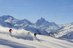 Skifahrer bei Abfahrt vor Bergpanorama Ski Arlberg
