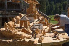 Tirler Schnitzer beim Schnitzen von Krippenfiguren (Tirler- Dolomites Living Hotel)