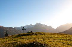Wanderer am Berggipfel mit Gipfelkreuz (Lech Zürs Tourismus)