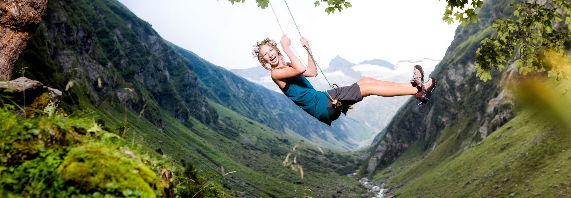 Mädchen beim Schaukeln vor beeindruckender Bergkulisse (Wildkogel Arena)